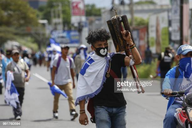 Masked protesters with a spear bomb take part in a protest against Nicaraguan President Daniel Ortega's government in Managua Nicaragua on July 04...