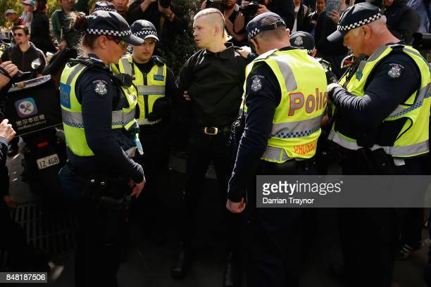A masked protestor is detained by police as they enforce laws surrounding the wearing of masks to cover the face at rallies on September 17 2017 in...