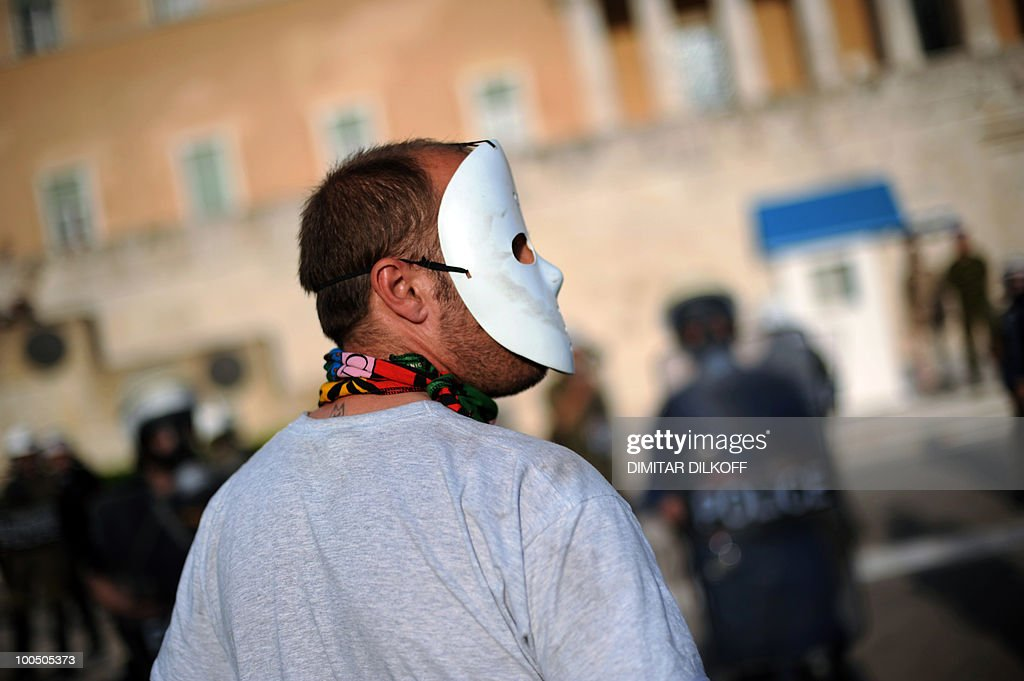 A masked protestor looks at a police cor
