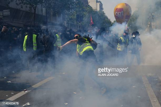 Masked protestors dressed in black stand in tear gas smoke during clashes with police prior to the start of the annual May Day rally in Paris on May...