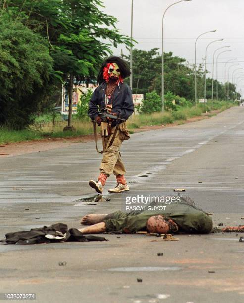 A masked rebel loyal to the warlord Charles Taylor passes 11 August 1990 by an ethnic Krahn death soldier of president Samuel Doe's troops in the...