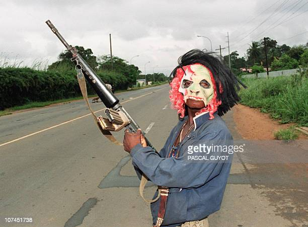 A masked rebel loyal to warlord Charles Taylor of the National Patriotic Front of Liberia holding a machinegun patrol in the streets of Monrovia 11...
