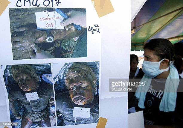 A masked rescuer walks past from pictures of dead bodies pasted outside a makeshift relief camp for identification in Khao Lak 30 December 2004 The...