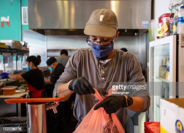 masked restaurant employee bagging up to-go order during covid-19 lockdown - food service occupation stock pictures, royalty-free photos & images