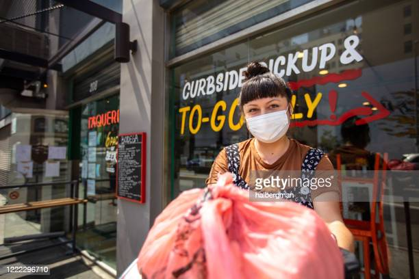 masked restauranteur during covid-19 lockdown holding out bagged order to camera - curbside pickup stock pictures, royalty-free photos & images
