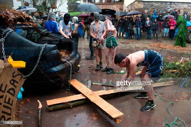 A masked reveller breaks a wooden cross during celebrations of the ancient carnival of Zubieta in the northern Spanish Navarra province on January 29...