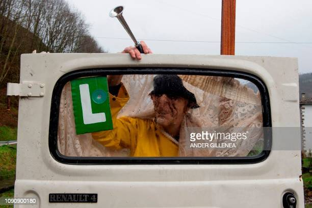 A masked reveller holds a car door during celebrations of the ancient carnival of Zubieta in the northern Spanish Navarra province on January 29 2019...