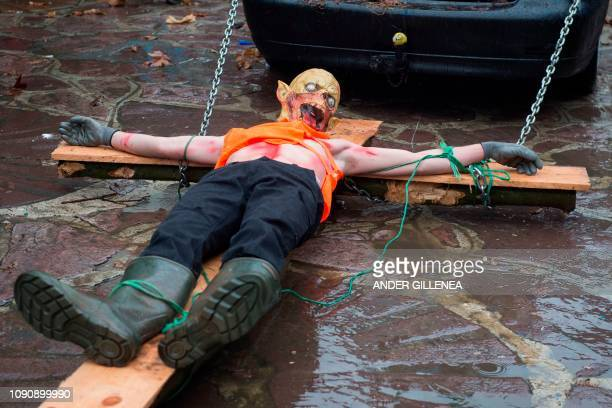 A masked reveller lies on a cross during celebrations of the ancient carnival of Zubieta in the northern Spanish Navarra province on January 29 2019...