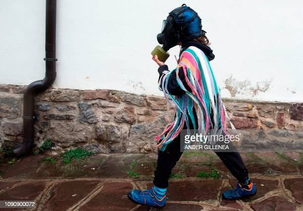 A masked reveller wearing a gas mask attends celebrations of the ancient carnival of Zubieta in the northern Spanish Navarra province on January 29...
