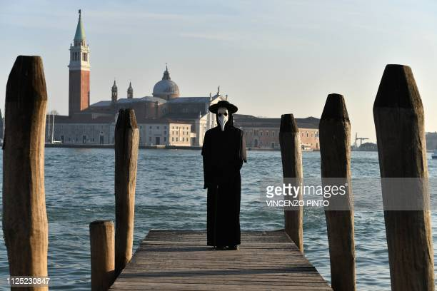 Masked reveller wearing traditional carnival costumes poses in font of the San Giorgio church in Venice on February 16, 2019.