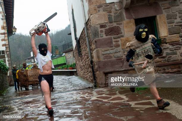 A masked reveller with a chainsaw runs after another participant during celebrations of the ancient carnival of Zubieta in the northern Spanish...