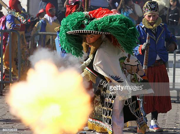 Masked revellers fire a rifle with gunpowder during a carnival in Huejotzingo Puebla state on February 24 2009 This carnival is a representation of...