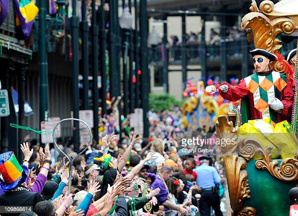 A masked rider in the Rex parade throws a cup to people in the crowd on Mardi Gras March 8 2011 in News Orleans Louisiana Mardi Gras or Fat Tuesday...