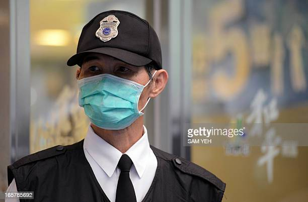 A masked security guard stand outside Taipei Hoping Hospital on April 6 2013 where new isolation units have been set up to treat potential new H7N9...
