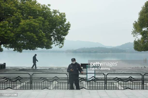 A masked security guard stands at the entrance to a park closed due to Covid19 in Hangzhou in east China's Zhejiang province Wednesday Feb 12 2020...