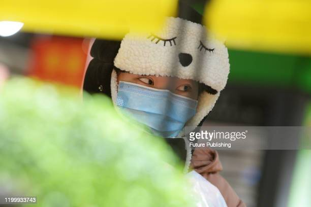 A masked shopper wearing a cartoon hood is seen in a supermarket in Wuhan the epicenter of the novel coronavirus outbreak in central China's Hubei...