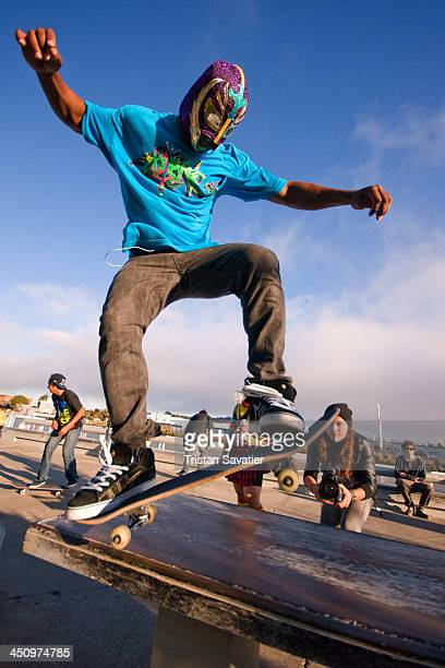 Masked skateboarder doing a wheelie at the annual Superhero Street Fair in San Francisco. Other keywords: skateboarding, skateboard, board, jumping,...