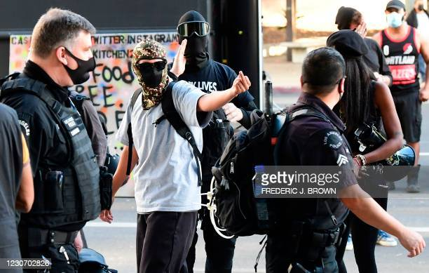 Masked social activist give the finger and make their feelings known to police officers walking by as a small crowd gathered to mark the inauguration...
