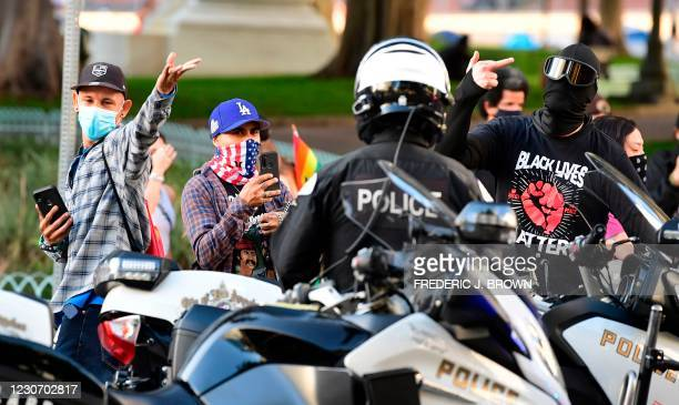 Masked social activists gesture and make their feelings known toward police officers as a small crowd gathered to mark the inauguration of Joe Biden...