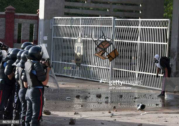 Masked student from the National Autonomous University of Honduras , takes part in clashes with riot police during a protest against the reelection...