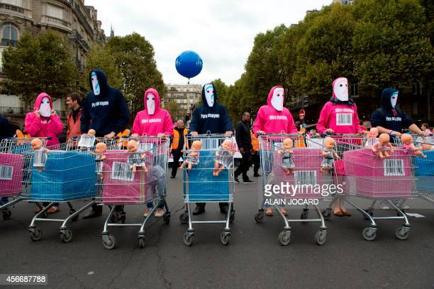 Masked supporters of the Antigay marriage 'La Manif Pour Tous' movement pose with baby dolls in trolleys during a protest against medically assisted...
