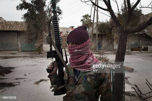 Masked Syrian Turkmen rebel takes posision in the Hanano district of the northern city of Aleppo on January 28, 2013. Members of Syria's Turkmen...
