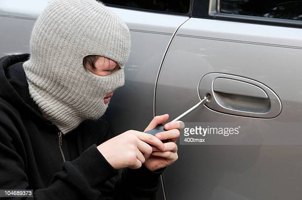 masked teenage boy breaking into a car - car alarm stock photos and pictures