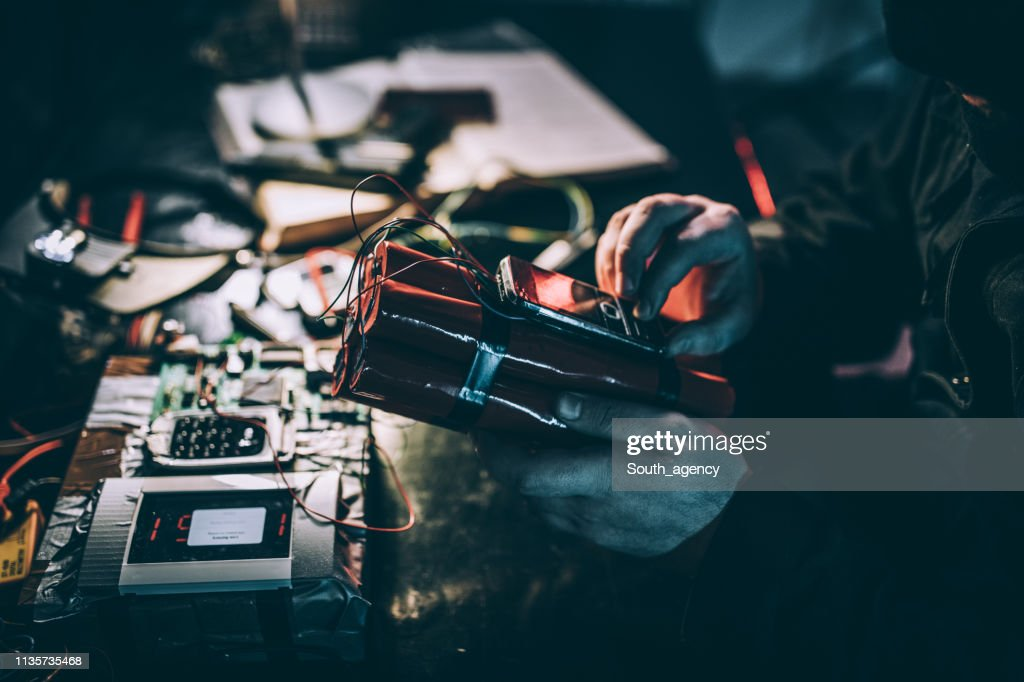 Masked terrorist with a dynamite bomb : Stock Photo
