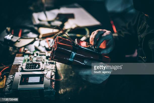 masked terrorist with a dynamite bomb - detonator stock photos and pictures