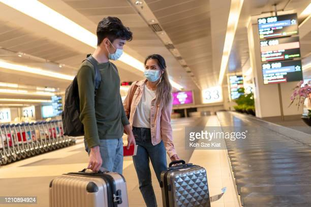 masked travelers at the airport - travel stock pictures, royalty-free photos & images