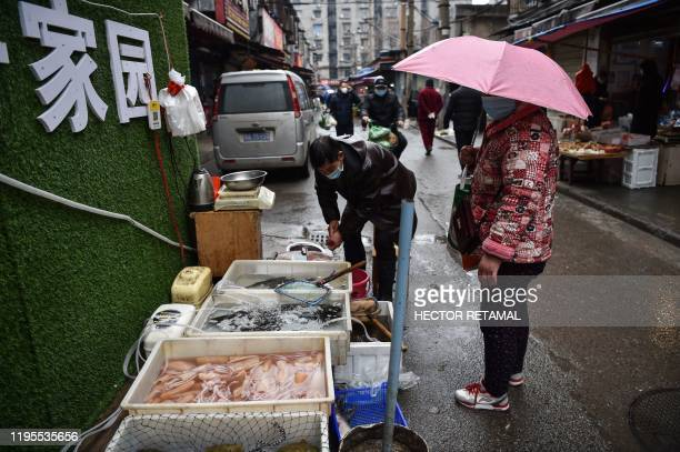 Masked vendor sells fish and turtles at a market in Wuhan where the coronavirus was discovered on January 24 2020. - The death toll in China's viral...