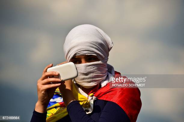 TOPSHOT A masked Venezuelan opposition activist uses her cellphone during a demonstration against Venezuelan President Nicolas Maduro in Caracas on...