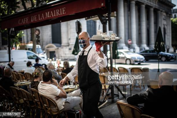 TOPSHOT A masked waiter works at the terrace of the Cafe de la Mairie on the Place SaintSulpice in Paris on June 2 as cafes and restaurants reopen in...