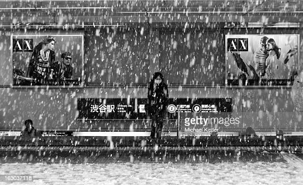 CONTENT] Masked woman emerging from the subway during a rare snowstorm in Tokyo She is flanked by ads from Armani Exchange Taken in Shibuya Tokyo...
