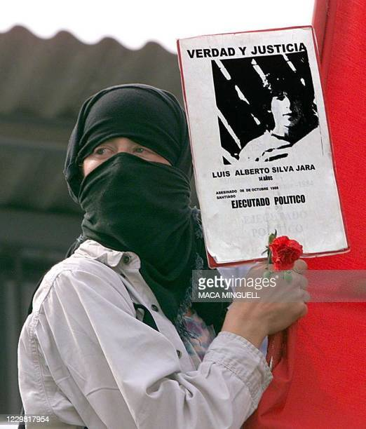 Masked woman holds a poster and a flower as thousands of Chileans take to the streets 11 September, 1999 in Santiago during a parade marking the 26th...