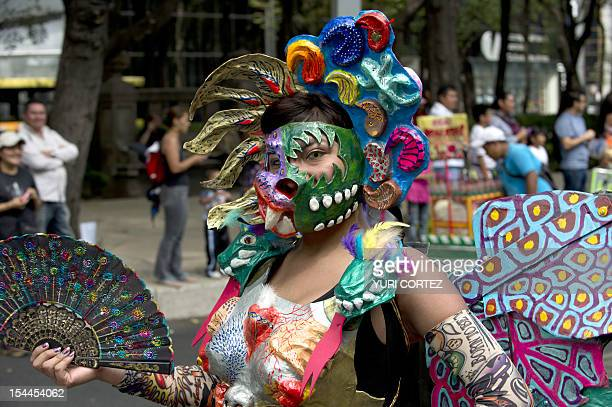 A masked woman participates in the Sixth Monumental 'Alebrijes' Parade on October 20 2012 in Mexico City Some 246 'Alebrijes' coloured Mexican folk...