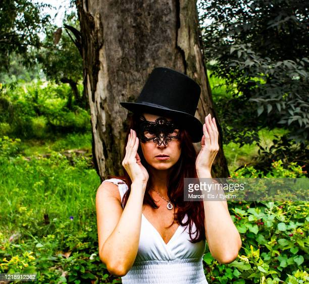 masked woman reaching for her mask - reality fernsehen stock pictures, royalty-free photos & images