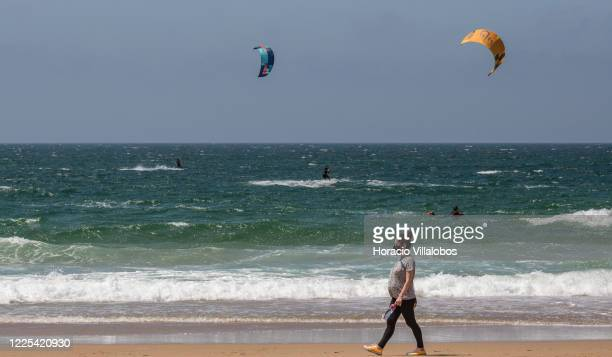 A masked woman walks along the shore while kite surfers ride the waves in Praia do Guincho during the COVID19 Coronavirus pandemic on May 17 2020 in...