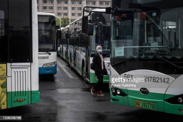 Masked woman walks between buses at a bus terminal in Wuhan in central China's Hubei province Wednesday, March 25, 2020. The city resumed the bus...