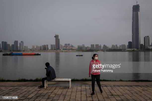 Masked woman walks in a riverside park after its re-opening in Wuhan in central China's Hubei province Wednesday, March 25, 2020.- PHOTOGRAPH BY...