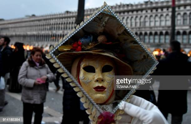 A masked woman wearing a traditional carnival costume looks at herself in the mirror in Saint Mark Square during Venice's Carnival on February 4 2018...
