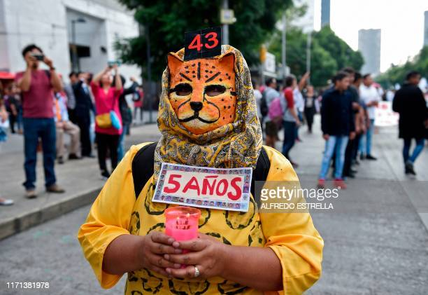 A masked woman with a sign reading 5 years takes part in a protest in Mexico City on September 26 to mark five years of the disappearance of the 43...