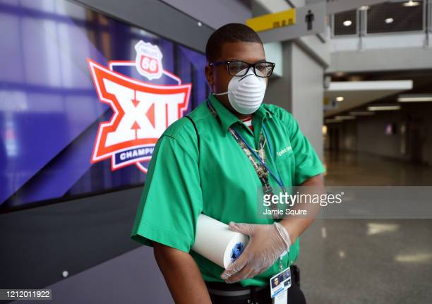 A masked worker cleans areas of the Sprint Center prior to the Big 12 tournament games at the Sprint Center on March 12 2020 in Kansas City Missouri