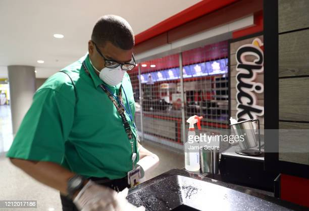 A masked worker cleans areas of the Sprint Center prior to the Big 12 tournament games on March 12 2020 in Kansas City Missouri