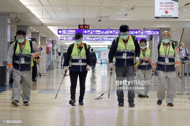 Masked workers disinfect a passenger throughfare at the Taoyuan International Airport on January 22 after Taiwan on January 21 reported its first...