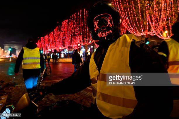 A masked yellow vest protestor poses near The Arc de Triomphe on the Champs Elysees in Paris on November 24 during a rally against rising oil prices...