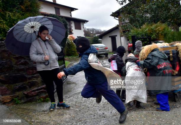 A masked young reveller throws dirt during the ancient carnival of Ituren in the northern Spanish Navarra province on January 28 2019 The yearly...