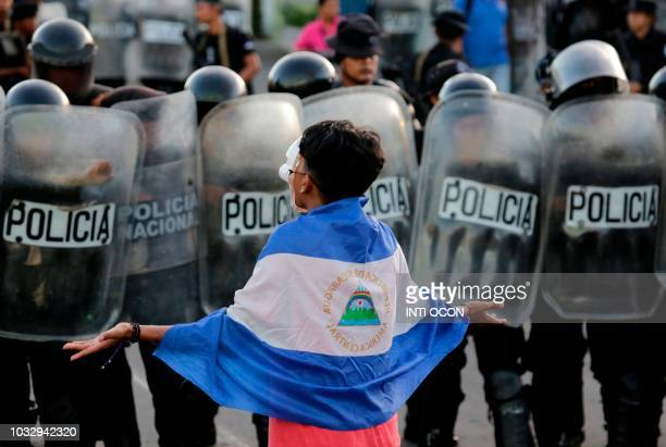 TOPSHOT A masked youngster protests against Nicaraguan President Daniel Ortega's government in front of a line of riot police blocking a street in...