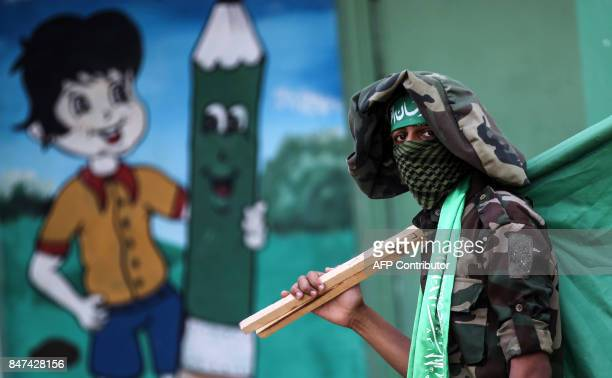 TOPSHOT A masked youth cadet of the Ezzedine alQassam Brigades the armed wing of the Palestinian Islamist Hamas movement carries the movement's flag...