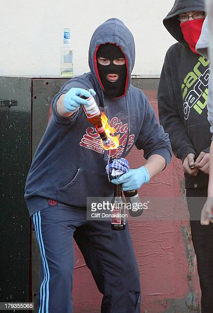 CONTENT] A masked youth wearing latex medical gloves to avoid leaving fingerprints lights a petrol bomb during rioting at Ardoyne Belfast where...